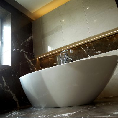 Natural stone Imperator gris with sandtone porcelaine - ambient illumination throughout with the feature V&A bath tub