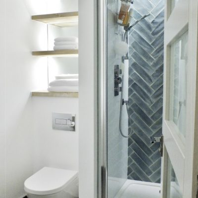 Feature aquamarine hatched tile with bright white paint finish and wood accents